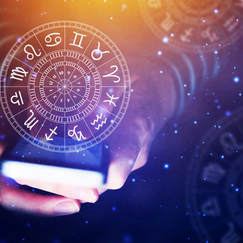 Astrology smartphone app concept, woman using mobile phone, close up of hands